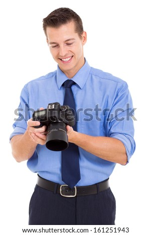 handsome photographer checking photos on his camera isolated on white background - stock photo