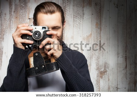 Handsome photographer is making photos with aspirations. He is standing and holding camera. The hipster with beard is smiling. Copy space in right side - stock photo