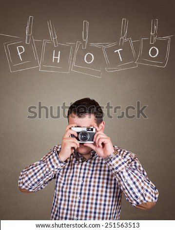 Handsome photographer man taking a picture with old retro (vintage) camera on old brown wall background with photo frames hanging on a rope held by clothespins design concept  - Photo text - stock photo