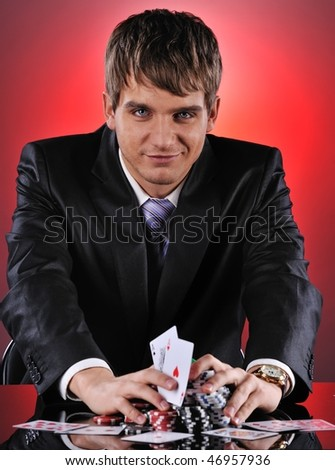 Handsome poker player with two aces in his hands - stock photo