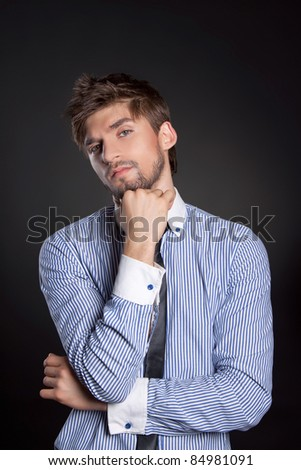 Handsome positive young business man standing and thinking - stock photo