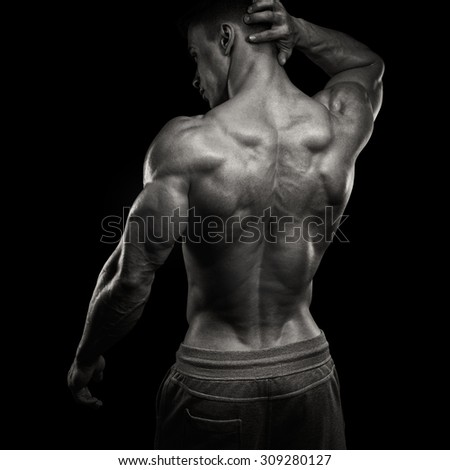 Handsome power athletic man turned back. Isolated over black background. Strong bodybuilder with shoulders, biceps, triceps and chest - stock photo