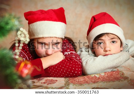 handsome preteen boy in christmas santa hat and tree - stock photo