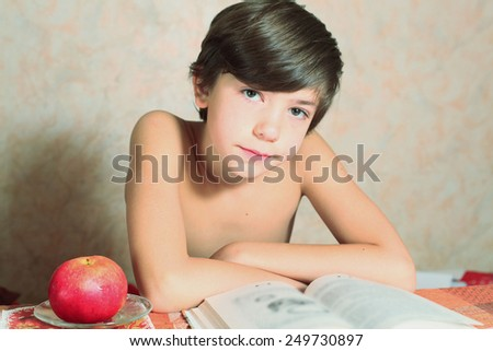 handsome preteen boy reading book with apple - stock photo