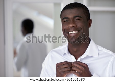 handsome professional african black man getting ready morning routine shirt at home for work - stock photo