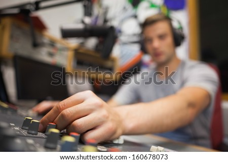 Handsome radio host moderating touching switch in studio at college - stock photo