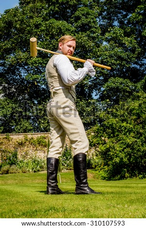 Handsome red haired man dressed in regency period costume playing croquet. Image with selective focus - stock photo