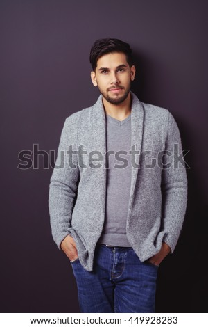 Handsome relaxed bearded young man in a stylish sweater and jeans standing leaning against a dark background with his hands in his pockets - stock photo