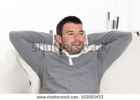 handsome relaxed man on sofa at home - stock photo