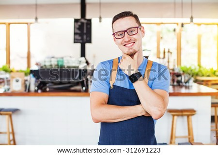 handsome restaurant owner standing in front of the coffee bar - stock photo