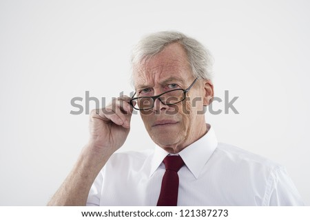 Handsome retired man in glasses peering over the top of the frames at the camera with a frown, head and shoulders studio portrait - stock photo