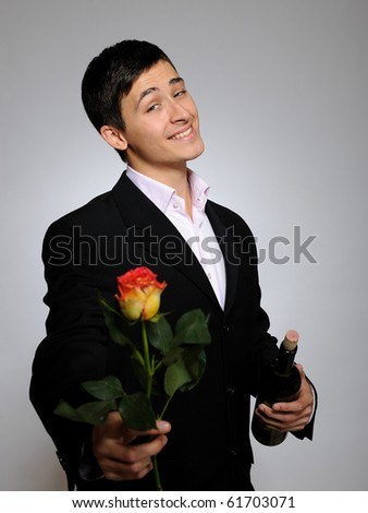 Handsome romantic young man holding rose flower prepared for a date. gray background - stock photo