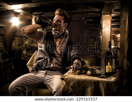 Handsome Rugged Male Pirate Drinking from Bottle in Ship Quarters - stock photo
