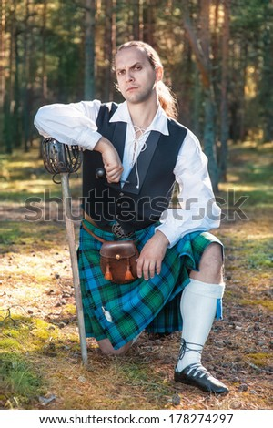 Handsome scottish man with sword and pipe  - stock photo