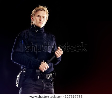 Handsome security officer with nightstick ensuring tough security for our safety - stock photo