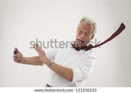 Handsome senior businessman being battered by strong winds with his tie whipping out behind him and his hands raised protectively conceptual of business adversity and disaster - stock photo