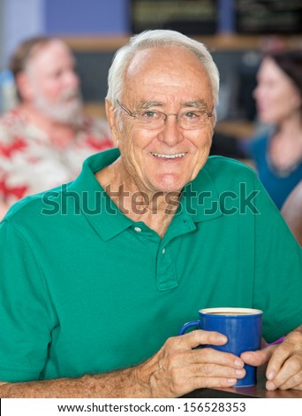 Handsome senior male smiling with coffee mug - stock photo