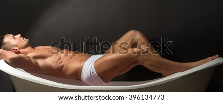 Handsome sensual sexy young stylish man in white panties bare muscular torso and beautiful body indoor lying on bathtub in bath room on studio background, horizontal picture - stock photo