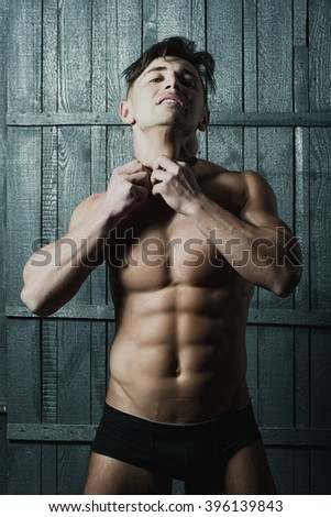 Handsome serious attractive male model man brunette looking straight with amazing naked strong torso cool biceps in black underpants tieing bow studio closeup on wooden background, vertical picture  - stock photo
