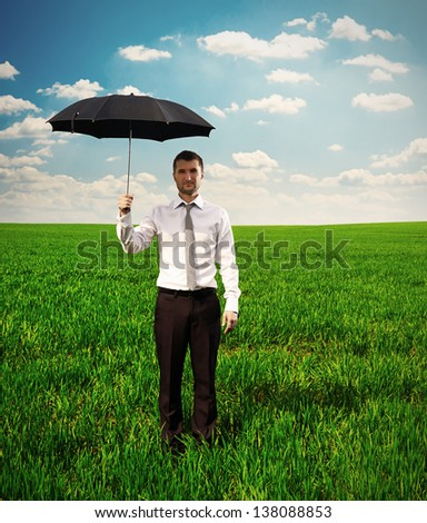 handsome serious man standing oh the green field and holding black umbrella - stock photo