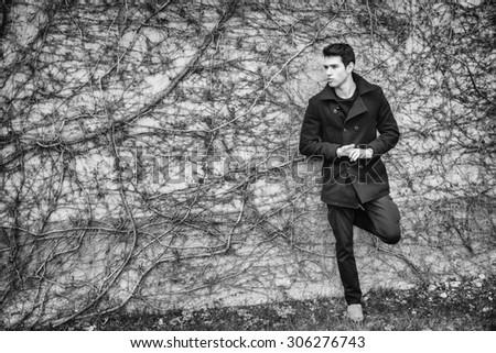 Handsome serious young man standing against plant covered wall, wearing winter clothes - stock photo