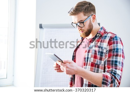 Handsome serious young man with beard in plaid shirt standing near flipchart and using tablet - stock photo