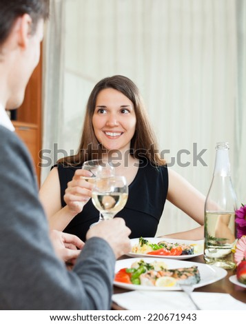 Handsome serving dinner for pretty girl at table in home interior - stock photo