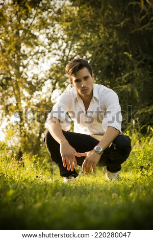 Handsome sexy man outdoors in the garden crouching down on fresh green grass amongst trees looking seductively at the camera - stock photo