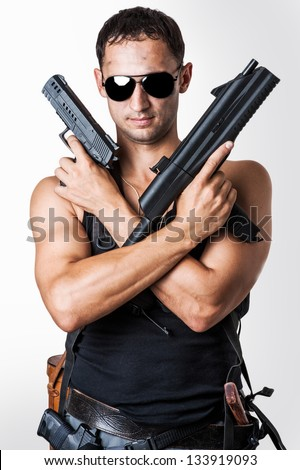 Handsome sexy  military man wearing black fashion sunglasses with automatic and hand gun - stock photo