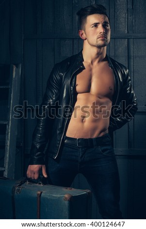 Handsome sexy sensual muscular stylish young man in leather jacket with bare torso standing with retro suit case near stairs indoor on wooden background, vertical picture - stock photo