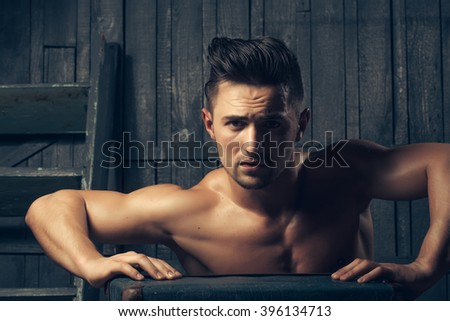 Handsome sexy sensual muscular stylish young man topless with bare torso and beautiful body sitting near stairs with hard big retro suit case indoor on wooden background, horizontal picture - stock photo