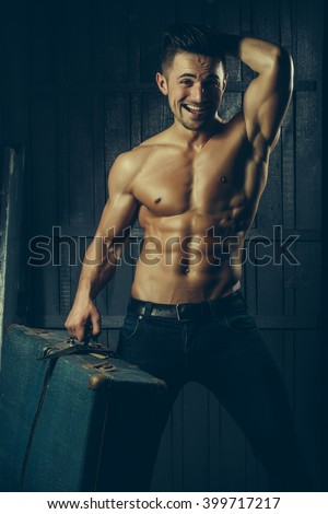 Handsome sexy sensual smiling muscular stylish young man topless with bare torso and beautiful body standing near stairs with hard big retro suit case indoor on wooden background, vertical picture - stock photo