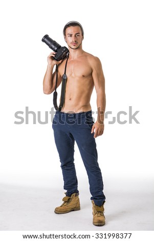 Handsome shirtless athletic young male photographer with professional photo camera in hand, isolated on white - stock photo