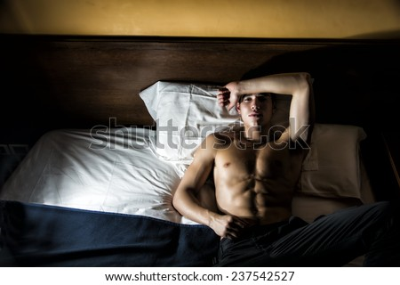 Handsome shirtless athletic young man laying in bed at night looking at camera - stock photo