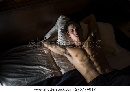 Handsome shirtless athletic young man laying in bed at night looking at camera, seen from above - stock photo