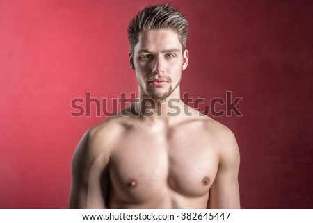 Handsome shirtless male model against a red background - Cute young man looking into camera - Bare chest - Confident - Healthy muscular athletic attractive fitness model - Red seductive background - stock photo