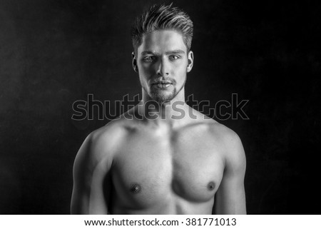 Handsome shirtless male model - Black and white photography - Young nude male against black background - Athletic young man looking straight seductive into camera - Young male fitness model - Fit body - stock photo