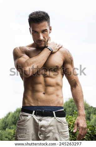 Handsome shirtless muscular young man outdoor, looking at camera - stock photo