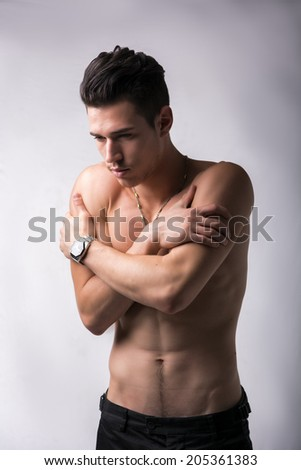 Handsome shirtless young man hugging himself while staring morosely at the floor as though comforting himself in his loneliness, on grey - stock photo