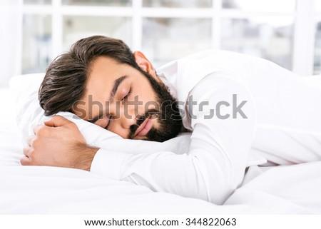 Handsome sleepy dark haired businessman with beard sleeping in white bed - stock photo