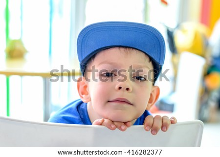 Handsome small boy in a blue baseball cap leaning his chin on the back of the chair giving the camera a pensive look - stock photo