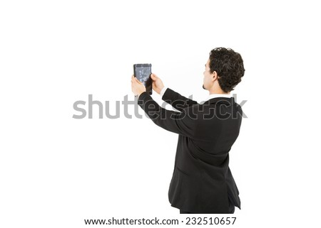 Handsome smart business man in a black and white suit and tie posing facing the back looking at computer screen - stock photo