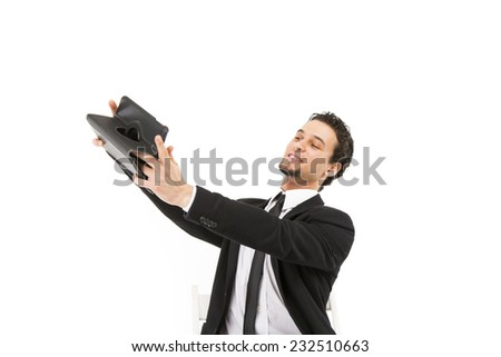 Handsome smart business man in a black and white suit and tie posing  holding up a small computer and smiling - stock photo