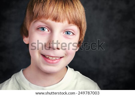 Handsome smiling boy in front of a grey background - stock photo