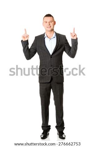 Handsome smiling businessman pointing upwards.  - stock photo