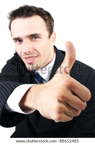 Handsome smiling businessmen (male model) showing thumb up as success sign and saying all right, OK - focus on hand, face out of focus -  head shot made in studio, isolated on white background - stock photo