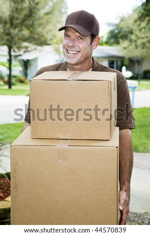 Handsome smiling delivery man carrying packages. - stock photo
