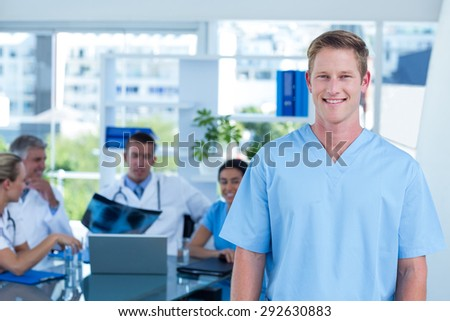 Handsome smiling doctor looking at camera in medical office - stock photo