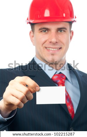 Handsome smiling engineer with hard hat on his head showing business card with space for your text. - stock photo
