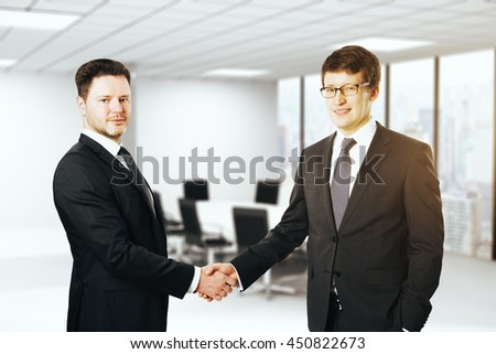 Handsome smiling european businessmen shaking hands and looking at the camera on blurry conference room interior background with city view - stock photo